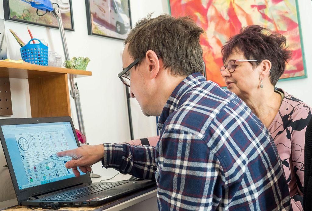 Valokuvassa asiakas ja Pirjo Mikkonen tutkivat tietokonetta